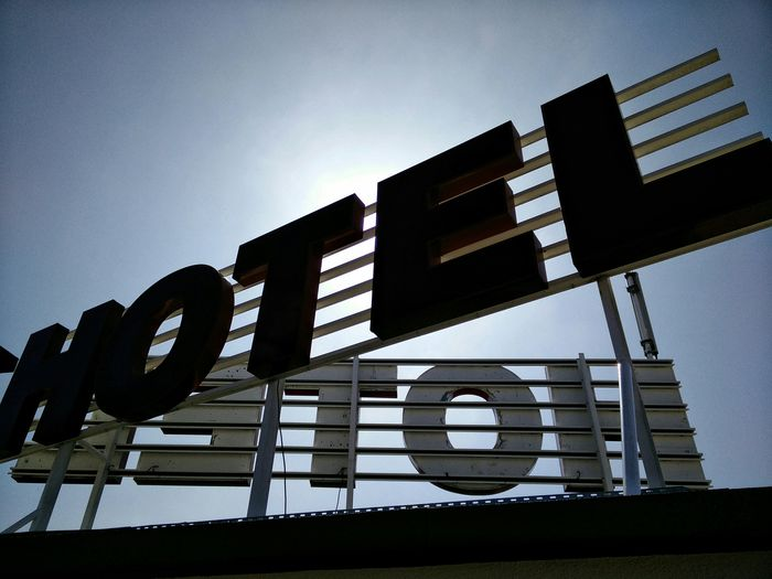 Low angle view of signboard on hotel against clear blue sky