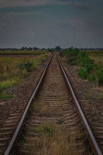 Railroad tracks on field against sky