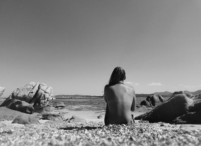 Rear view of topless sensuous woman sitting at beach against sky