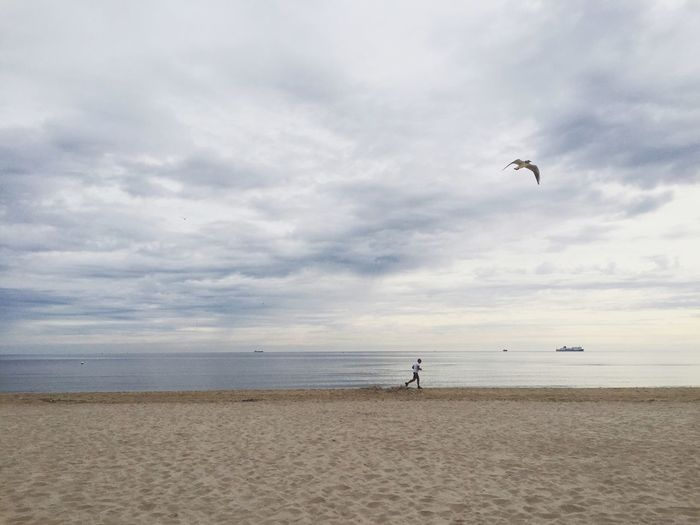 Side View Of Man Running On Calm Beach