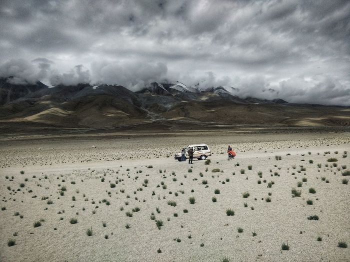 People At Desert Against Cloudy Sky