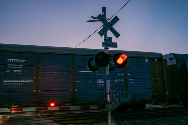 Sign Guidance Communication Signal Railway Signal Transportation Rail Transportation Light Stoplight Railroad Crossing Text Illuminated No People Western Script Architecture Directional Sign Crossing Sign Safety Sky Information Outdoors Train