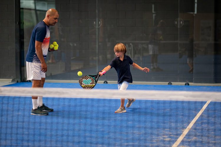 Monitor teaching padel class to child, his student - trainer teaches little boy how to play padel