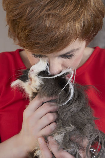 Close-up of woman kissing guinea pig