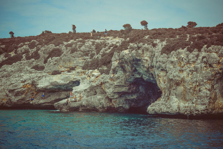 People On Rocks Water Sea Rock Sky Scenics - Nature Rock - Object Waterfront Beauty In Nature Nature Tranquil Scene Solid Day Rock Formation Land Tranquility Outdoors Blue Eroded Sea Cave Coastline
