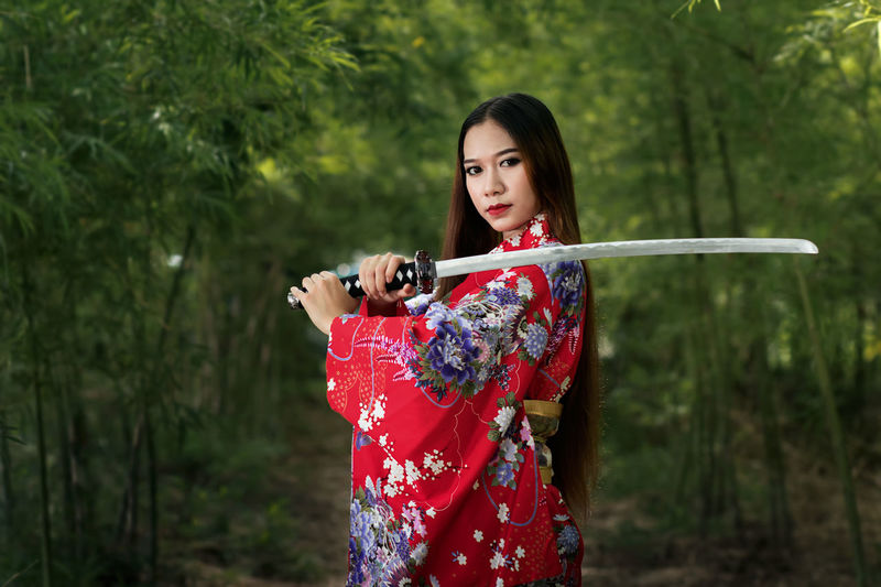 Portrait Of Young Woman Holding Sword While Standing In Forest