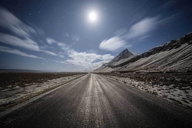 Country road amidst landscape against sky at night