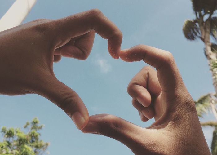 Cropped hands of couple making heart shape against sky