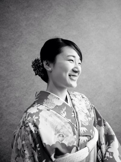 Smiling Young Woman Wearing Kimono Against Wall
