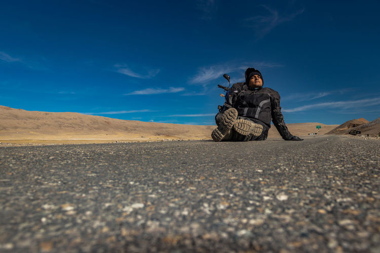 Man sitting on road at desert against sky
