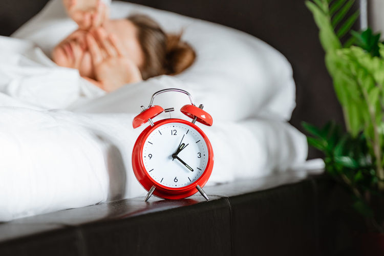 Young woman waking up in white bed yawning rubbing eyes turning alarm clock in bedroom.