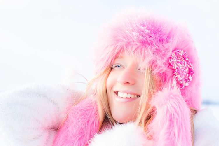 Portrait of beautiful young woman with pink fur hat