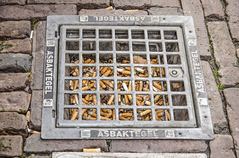 High angle view of text on metal grate on footpath