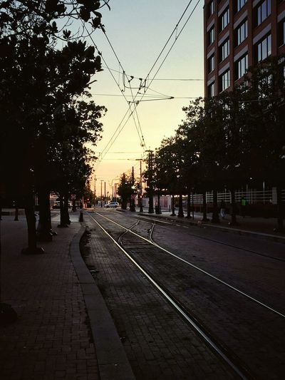 Power Lines Buildings Roadways Dusk In The City City Tree Sunset Railroad Track Public Transportation Silhouette Rail Transportation City Life Sky Travel Tramway Track Railway Track