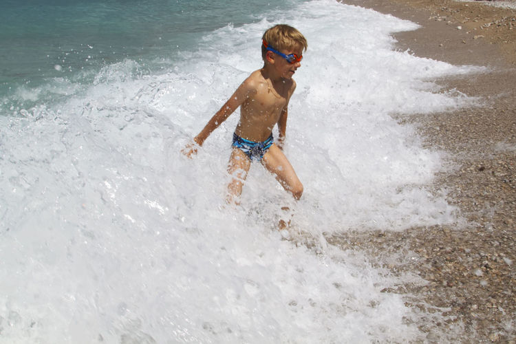 Full length of shirtless boy standing in wave at beach