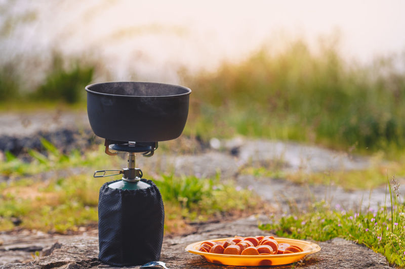 Campstove kitchen on coastal rocks Beauty In Nature Camping Camping Stove Close-up Coastal Feature Cooking Dinner Food Food And Drink Freshness Grass Healthy Eating Hiking Lifestyles Nature No People Outdoors Pasta Ready-to-eat Sausage Sunset