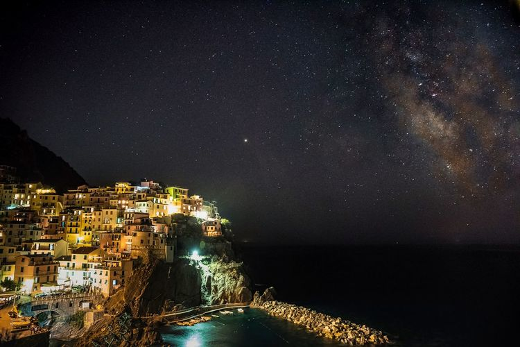 Aerial view of illuminated city by sea against sky at night