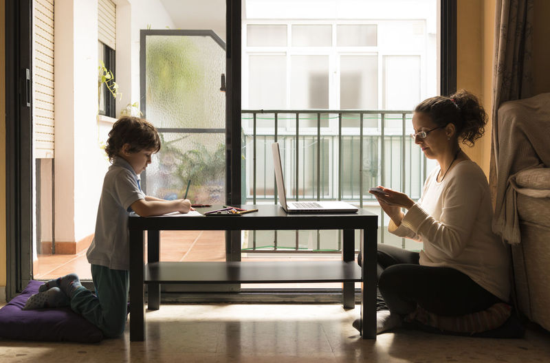Side view of woman working while son studying at table during lockdown