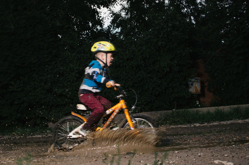 Side View Of Boy Riding Bicycle On Muddy Field