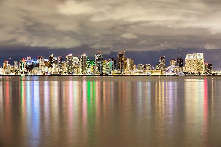 Illuminated Buildings By Sea Against Sky