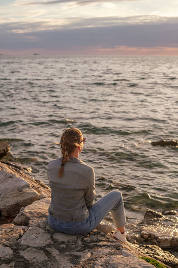 Rear view of woman sitting on rock against sea