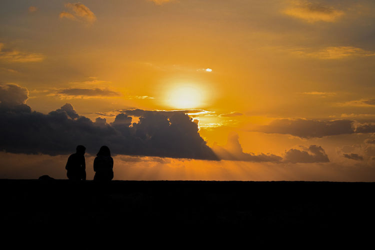 Silhouette couple against orange sky during sunset