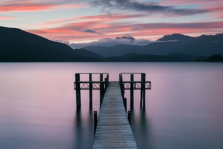 Wooden jetty in lake against sky during sunset