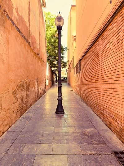 Empty footpath amidst buildings in city
