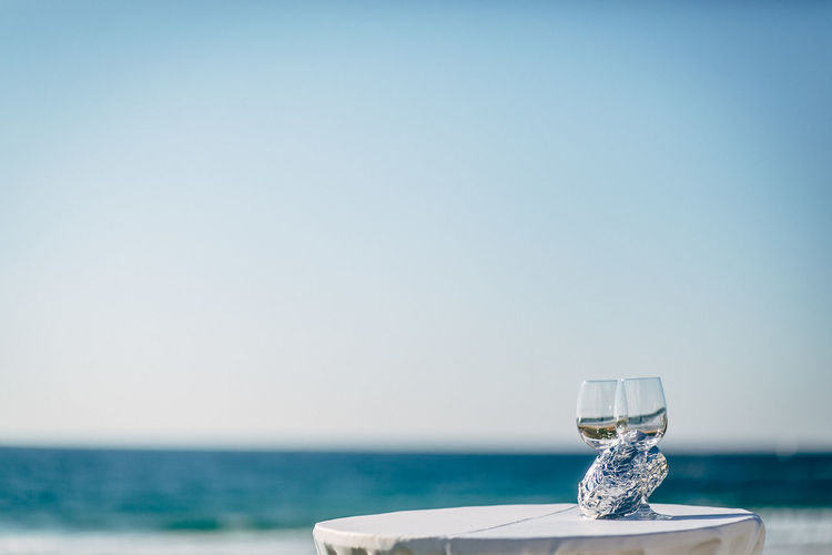 View of drink on table at sea against clear sky