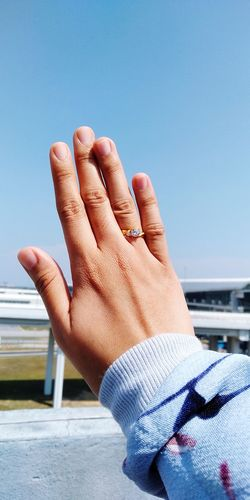 Cropped Hand Of Woman With Ring Against Clear Sky