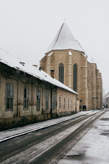 Church by road against clear sky during winter