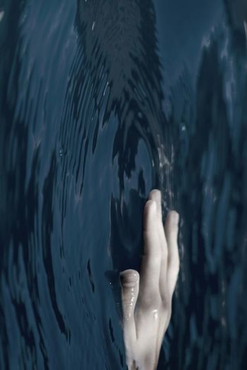 Cropped image of hand on lake