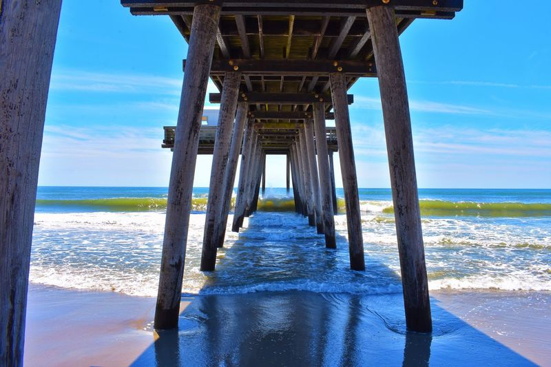 Below View Of Pier At Beach Against Blue Sky During Sunny Day