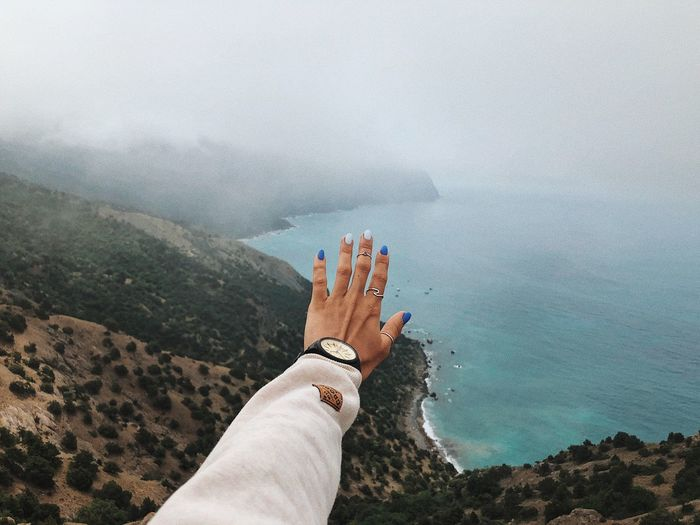 Low section of person hand by sea against sky