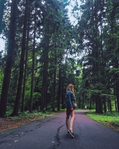 Woman walking on road amidst trees in forest