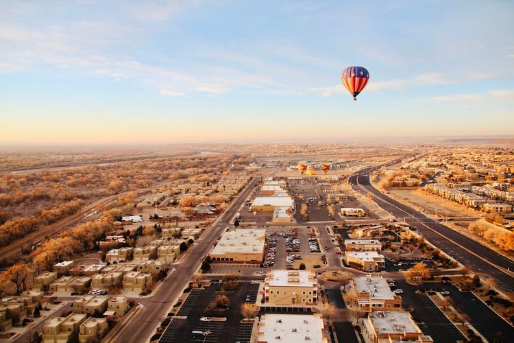 Aerial view of hot air balloon flying over city