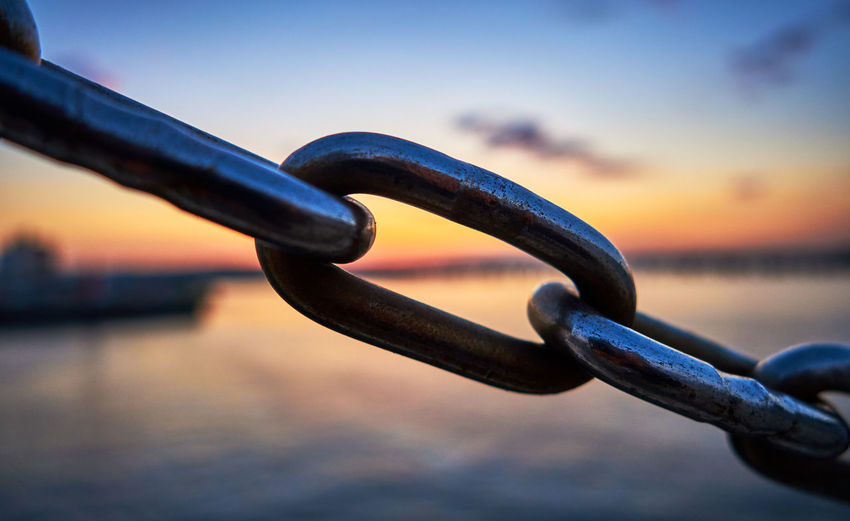 Close-up of chain against sea during sunset