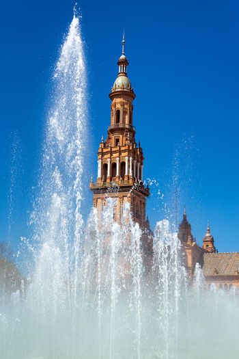 Vertical view of the fountain in the Plaza de Espana with ornate architecture in the background in Seville, Spain Seville Sevilla Architecture Built Structure Building Exterior No People Europe SPAIN Travel Travel Destinations Tourism Façade Medieval European  Spanish Sky Plaza De España Fountain Water Tower Motion Building Blue Spire