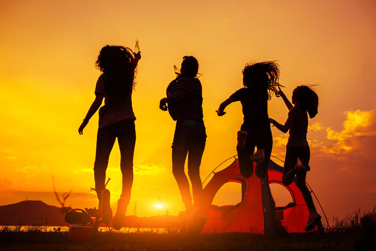 Silhouette Group of women party with drink bottles and jumping enjoy travel camping,trekking in vacation time at sunset. Sunset Sky Orange Color Group Of People Nature Leisure Activity Silhouette Land Lifestyles Real People Full Length Women Friendship Child Beauty In Nature Men Togetherness Sun Sunlight Outdoors