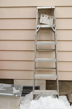 Old worn aluminum ladder with broken tool tray outdoors leaning against a wall with snow on the ground. Copy Space Ladder Weathered Aluminum Broken Tool Tray Day Exterior Wall No People Old Outdoors Snow Vinyl Siding Worn