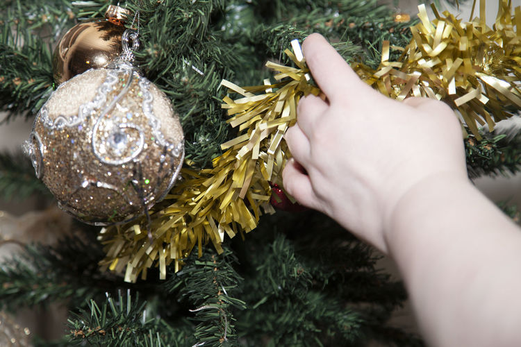 Close-up of hand holding tinsel
