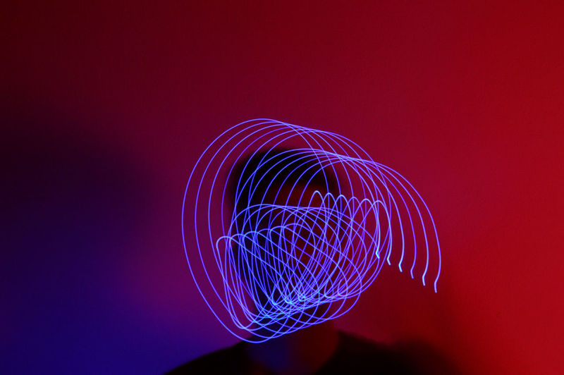 Close-up of illuminated light painting against red background