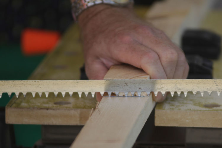 Cropped Hand Of Carpenter Cutting Wood