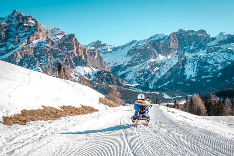 People riding motorcycle on snowcapped mountains against sky