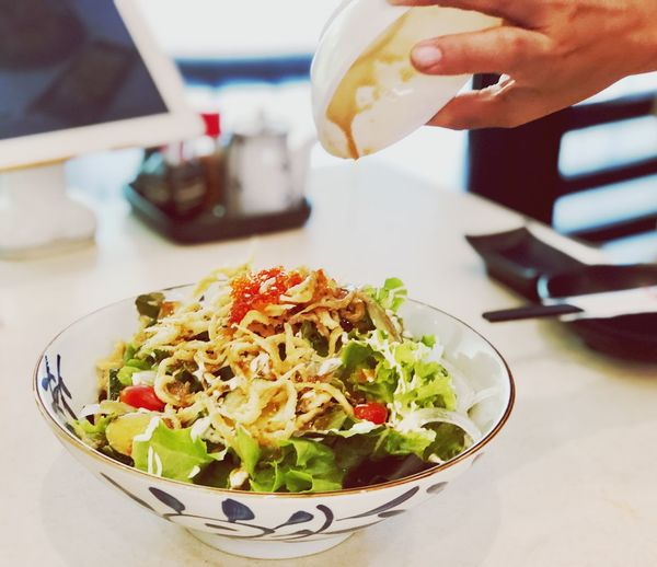 Pouring salad dressing in a Japanese salad. Human Hand Food And Drink Food Hand Human Body Part One Person Freshness Ready-to-eat Vegetable Wellbeing Salad Real People Focus On Foreground Table Unrecognizable Person Indoors  Lifestyles Healthy Eating Holding Bowl