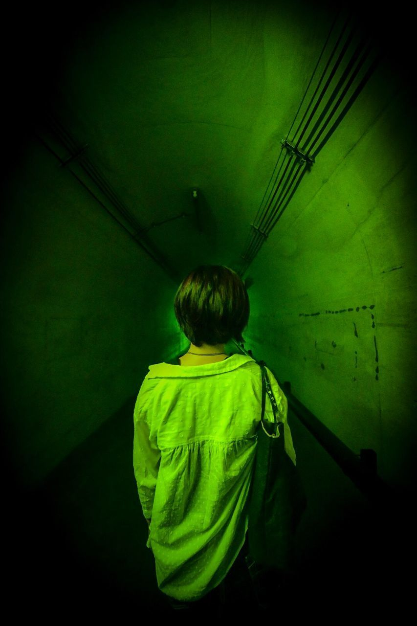 REAR VIEW OF BOY STANDING IN ILLUMINATED GREEN