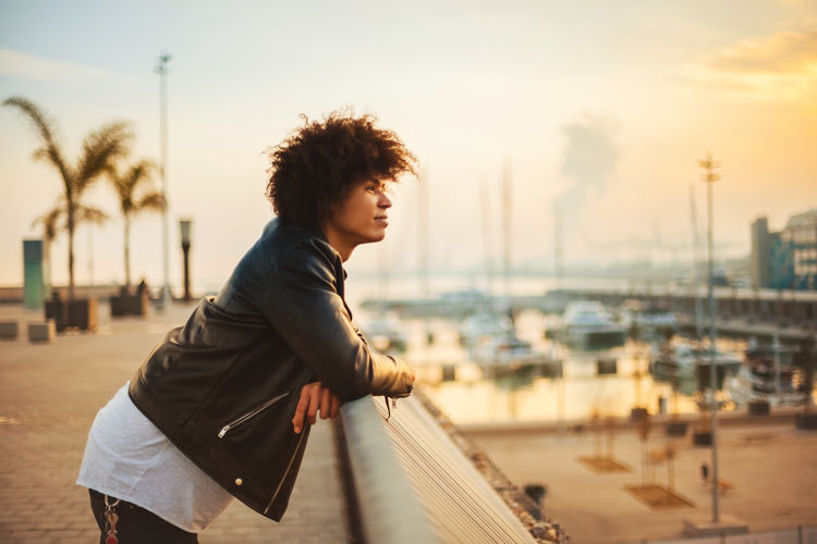 Young man looking away standing by railing during sunset