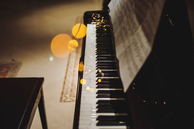 High angle view of illuminated string lights over piano at home