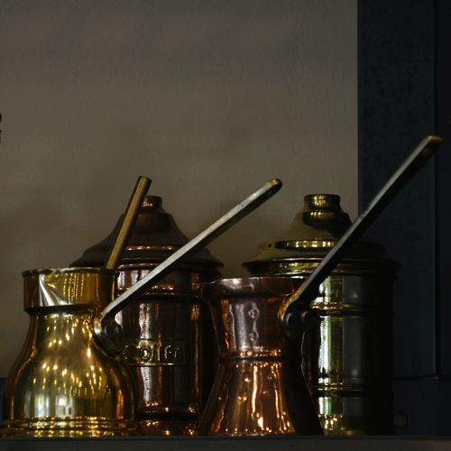 Old-Fashioned Coffee Pots On Table Against Wall