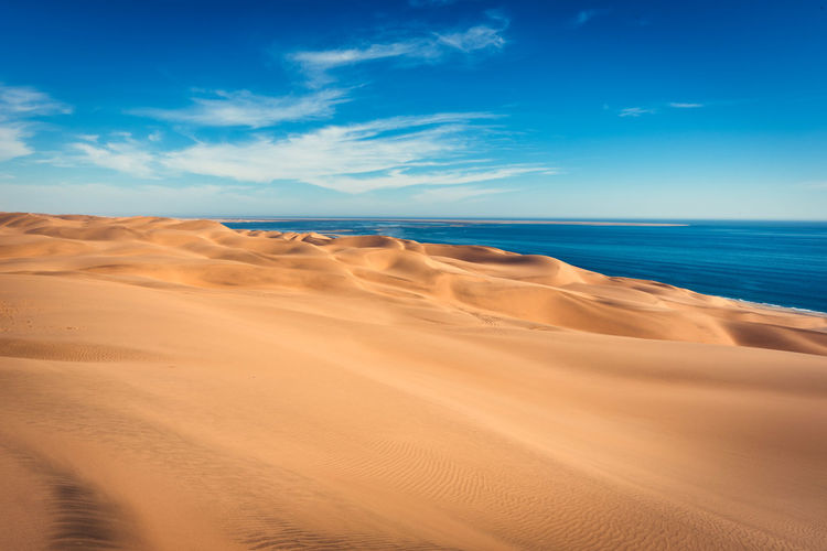 Scenic view of sand dunes by sea against blue sky